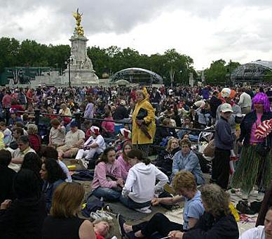 Crowds gather outside Buckingham Palace to watch the pop concert on big screens during celebrations to mark The Queen's Golden Jubilee, 2002. © Press Association